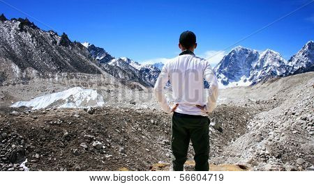 Rear View of Hiker standing in the Khumbu Valley with the Himalayan Mountain Range in background near Gorak Shep in the Sagarmatha (Mount Everest) National Park in Nepal