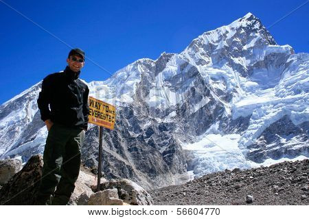 Man standing next to signpost to the Mount Everest Base Camp with Nuptse mountain in the background, Nepal