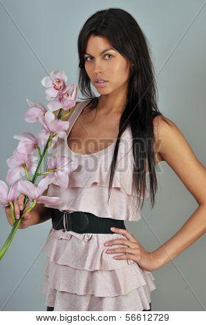Attractive brunette model holding orchid flower