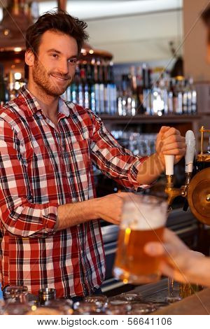 Portrait of young bartender tapping beer in pub, looking at customer, smiling.