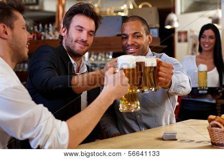 Amigos felices chocan con jarras de cerveza en pub, sonriendo.