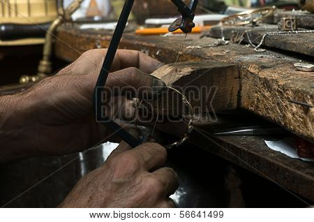 Traditional goldsmith cutting gold bracelet