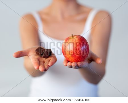 Close-up Of Woman Showing Chocolate And Apple Focus On Apple