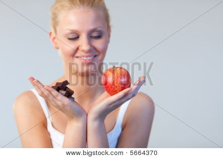 Beautiful Woman Showing Chocolate And Apple Focus On Chocolate And Apple