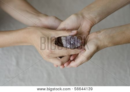 Womans hands giving an amethyst crystal one to another
