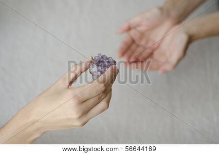 Womans Hands Giving An Amethyst Crystal  To Another