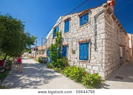 Beautiful old stone house with blue window shutters in Susak, Croatia.