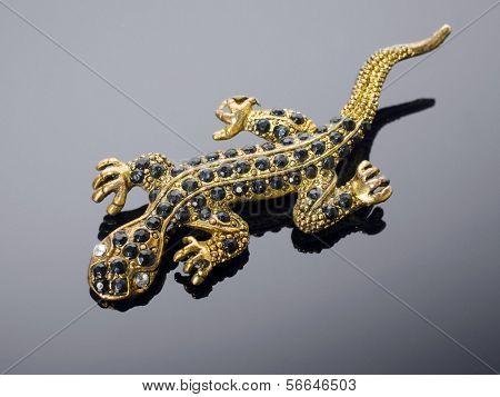 Golden lizard (brooch) on grey background.