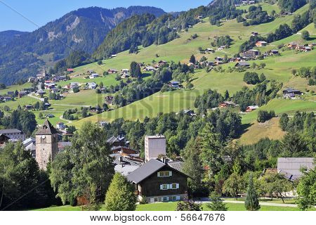The charming landscape in the French Alps. Sunny Sunday afternoon in the Haute-Savoie. Green alpine meadows and lovely houses - chalets