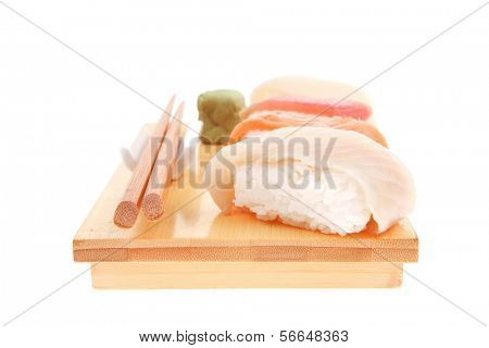 Japanese Cuisine - Different Types of Nigiri Sushi : Tuna (maguro) Salmon (sake) and Eel (unagi) with Wasabi on wooden plate isolated over white background