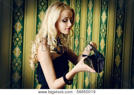 Beautiful blonde woman looking into her purse.