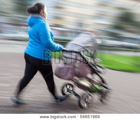Mother With Small Children And A Pram Walking Down The Street