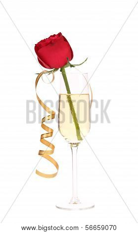 Red rose in glass of champagne and paper streamer.
