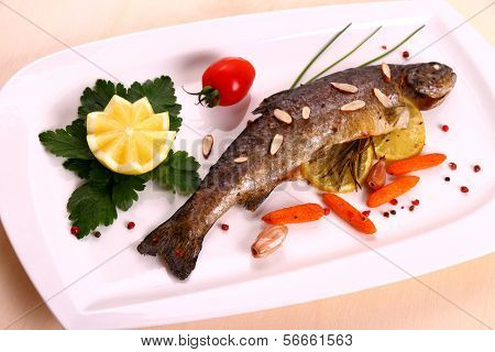 Fried Trout With Lemon And Split Almonds On White Plate