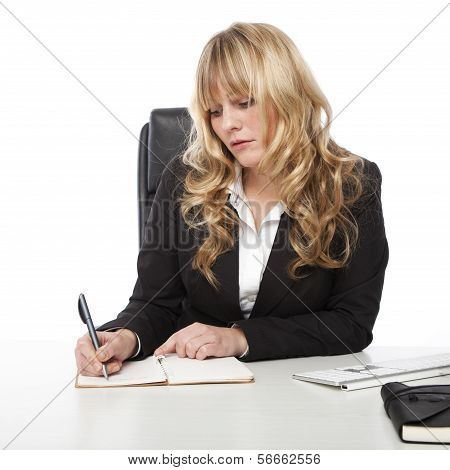 Young businesswoman writing in her diary