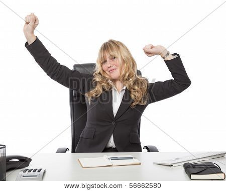 Contented businesswoman stretching at her desk