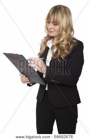 Businesswoman writing notes on a clipboard