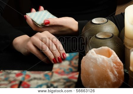 Hands of young woman with divination cards