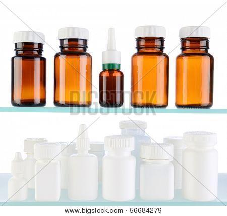 A variety of medicine bottles on glass shelves. Bottles have no labels, over a white background.