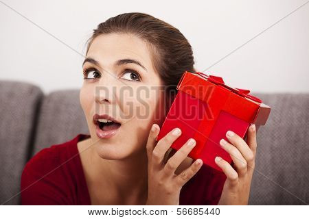 Beautiful and happy woman trying to guess what is inside the christmas present