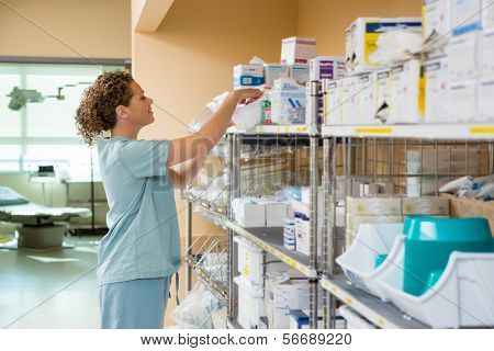 Side view of female nurse working in storage room of cancer hospital