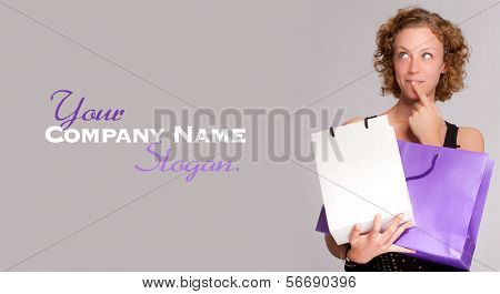 Young blond woman hesitating with two shopping bags