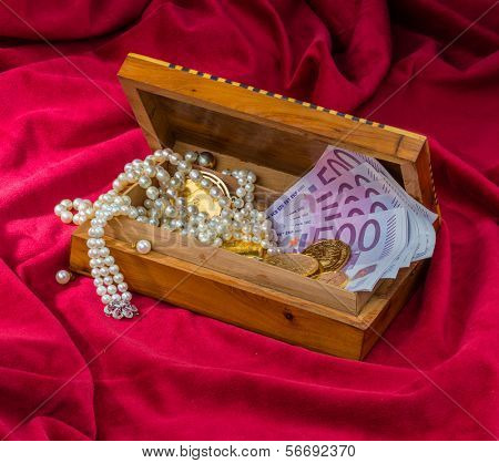 gold coins and bars with decorations on red velvet. symbolic photo for wealth, luxury, wealth tax.