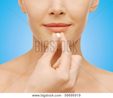 healthcare and medical concept - closeup picture of beautiful woman with pill