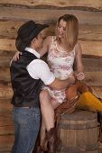 picture of western saddle  - A western couple is talking while she is sitting on a saddle - JPG
