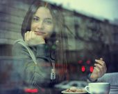 stock photo of cafe  - Young woman drinking coffee and reading book sitting indoor in urban cafe - JPG