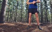 stock photo of stopwatch  - Man looking at stopwatch to check gps pace and time on trail run - JPG