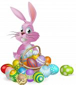 stock photo of easter basket eggs  - Pink Easter bunny rabbit with Easter eggs basket full of chocolate decorated Easter eggs - JPG