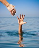 stock photo of sky diving  - helping hand giving to drowning man in sea - JPG