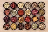 Large chinese herbal medicine selection in wooden bowls over papyrus background.