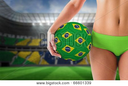 Fit girl in green bikini holding brazil football against large football stadium with brasilian fans