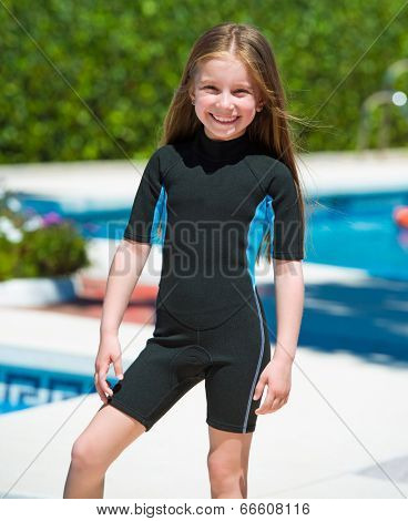 happy little girl in a wetsuit near the pool in the summer