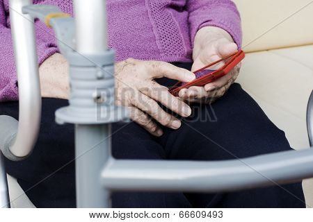 Elder Woman With A Smartphone And Orthopedic Walker