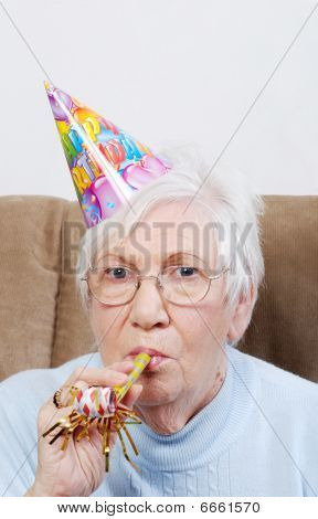 Senior Woman With Birthday Hat And Noise Maker