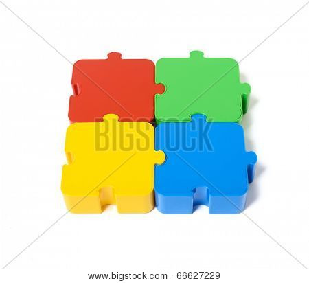 Four colored puzzle pieces close up