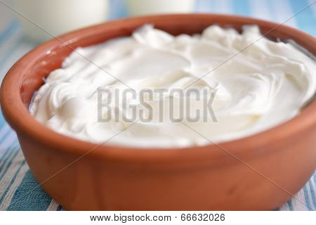Pot with strained yogurt closeup. Selective focus