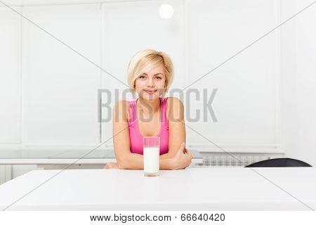 woman drink glass of milk in her kitchen