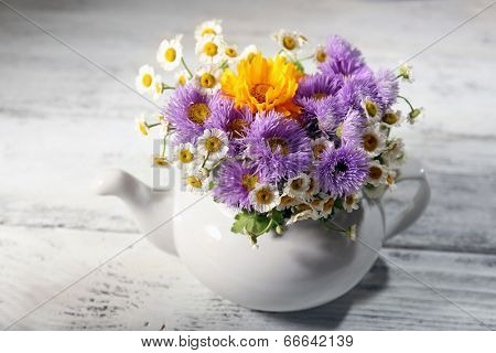 Kitchen decoration with teapot and wild flowers on wooden background