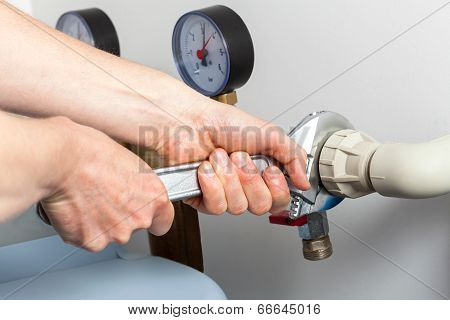 Hands Repairing Valves In Boiler Room