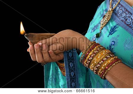 Diwali or festive of light. Traditional Indian festival, woman in sari hands holding oil lamp.