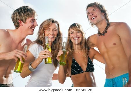 Four people celebrating beach party