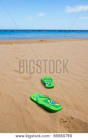 green sandals on sandy beach