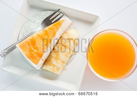 Top View Of Banana Caramel Crepe Cake And Orange Juice On White Background
