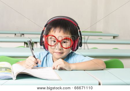 Smart student writing and wearing headphone in the classroom
