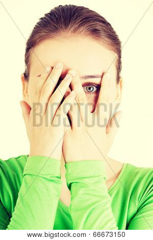 Shy or scared teenage girl peeking through covered face.