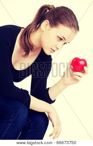 Pretty woman in depression holding small heart in her hand.